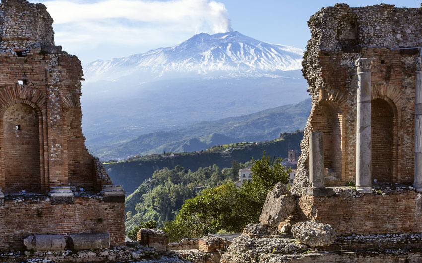 Etna seen through the Ancient Amphitheater in Taormina