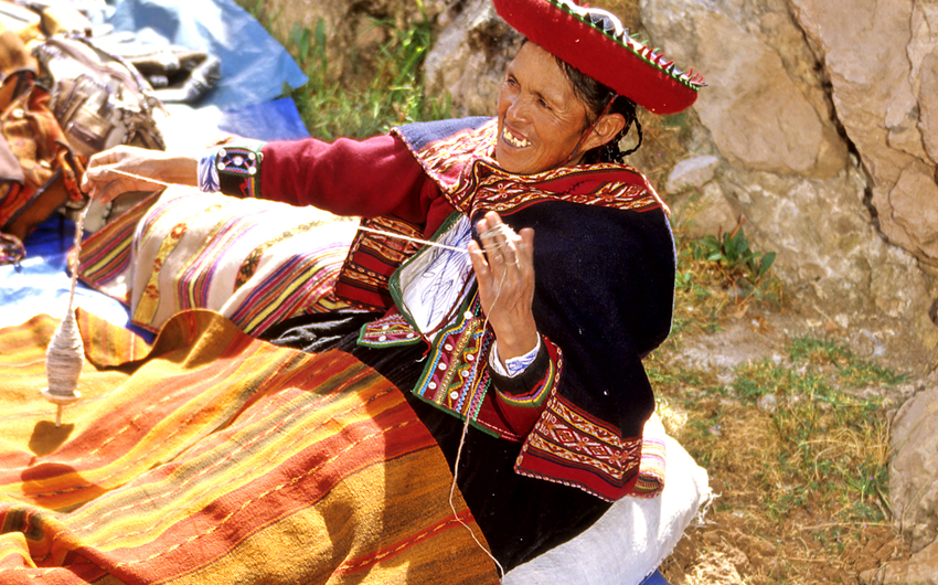 Traditionally dressed woman selling blankets in Sacred Valley market