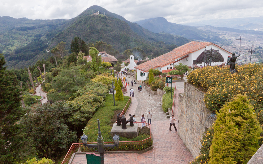 Tourists at Monserrate Hill with yellow blooming flowers and its historical buildings, Bogota