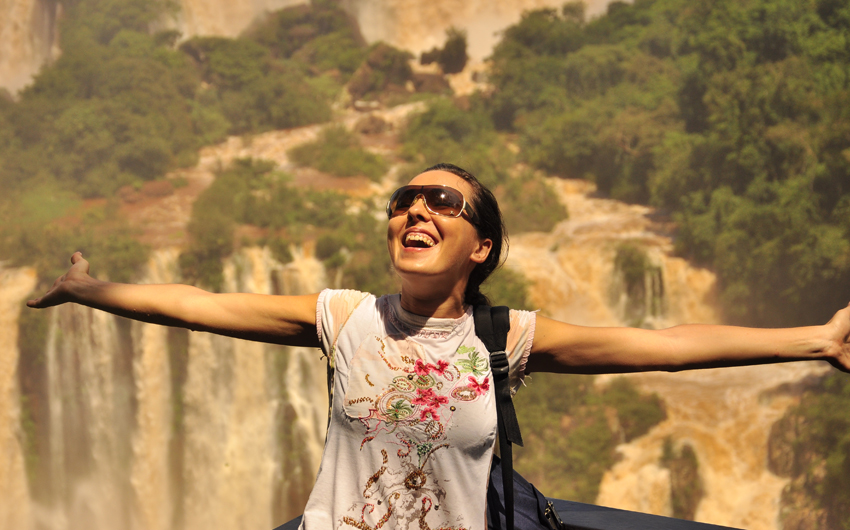 Happy woman enjoying the Iguazu waterfall Argentinian side.Iguazu Falls is located where the Iguazu River tumbles over the edge of the Paran