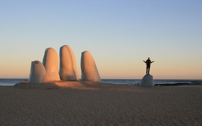 Big hand on the beach, sunset at the beach, person above finger, sea cost blue sky uruguay punta del este giant sand ocean